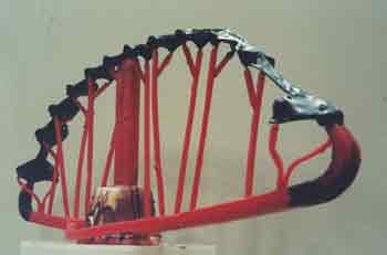 Image of dark wax form with red wax sprues attached