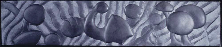 Image of a long horizontal black slate carving with various organic forms.