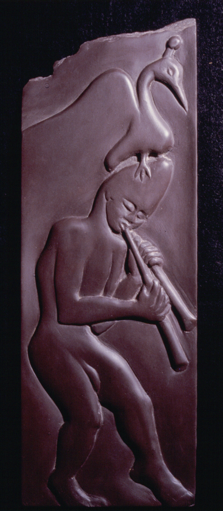 Image of carving on roofing slate of a walking male figure with large bird on his head playing pipes.