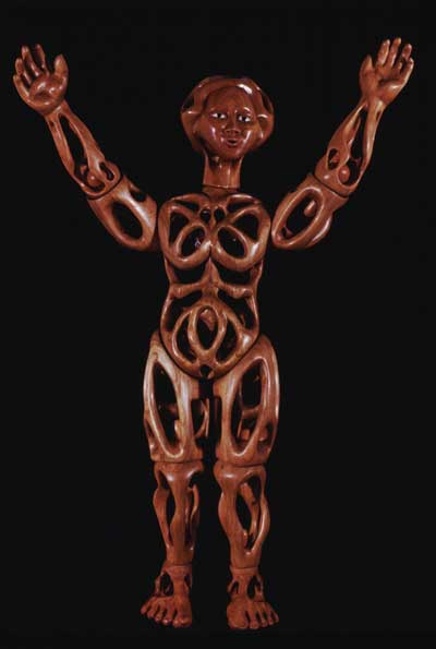 Image of perforated wooden doll with arms raised.